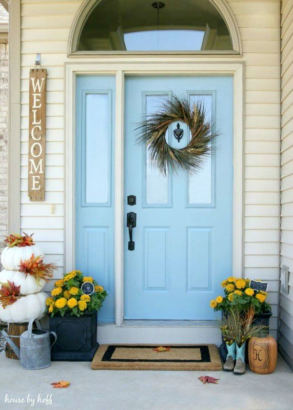 Light blue front door with fall wreath and yellow flowers in planters.