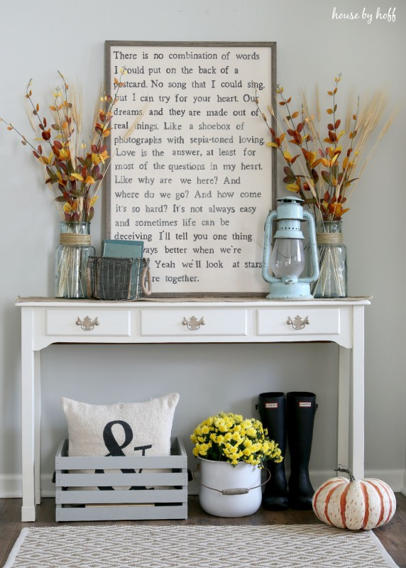 Side table with picture of a phrase on it and boots and pumpkin under it.