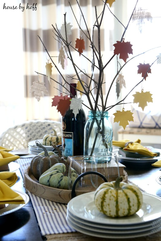 Green and white pumpkins on white plates on table.