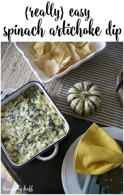 Spinach artichoke dip with mini pumpkins and chips on table.