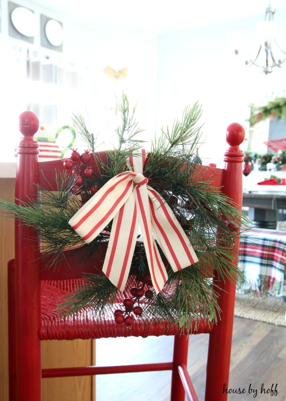 Holiday bar stool painted red, with a sprig of evergreen, red berries and a bow.
