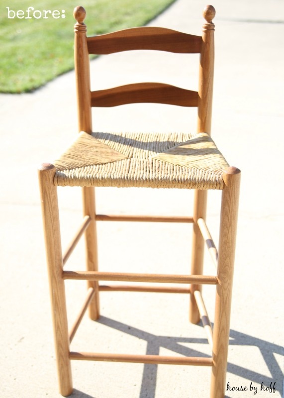 A wooden and wicker bar stool outside by the grass.