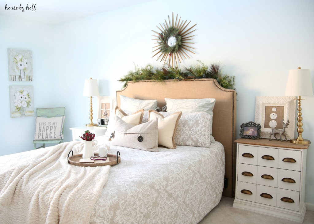 Neutral bed and pillows with a green wreath above the bed.