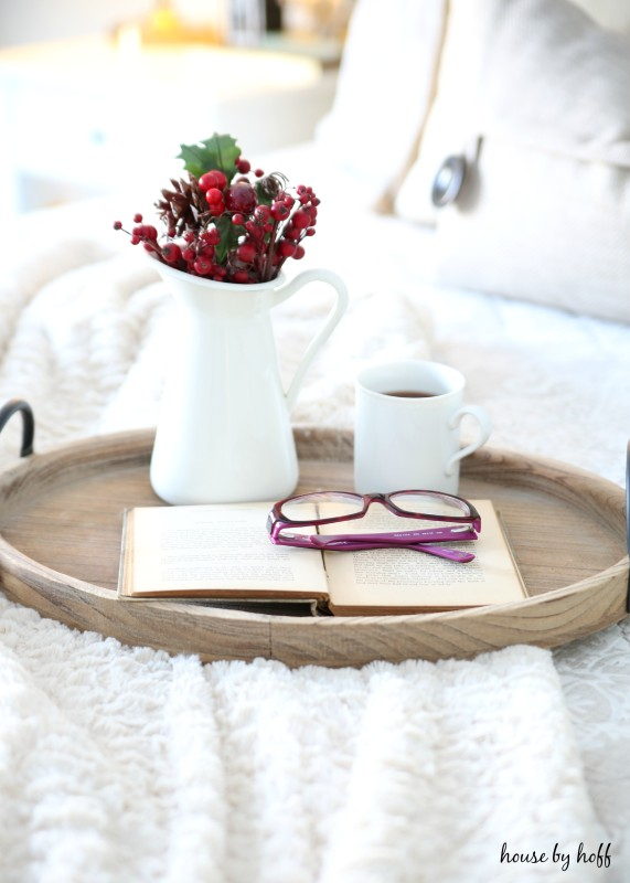 A cut of tea, berries, glasses and a book on the wooden tray on the bed.