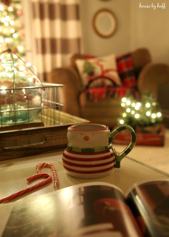 A snowman mug and candy canes on the table.