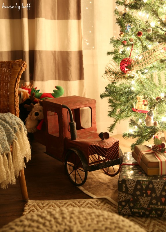 An antique looking toy truck is under the tree.