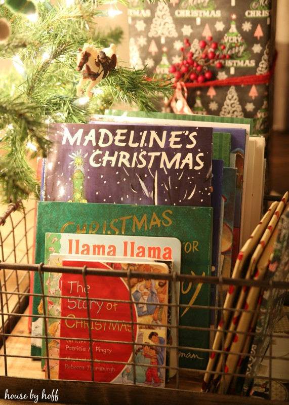 Christmas books in a wire basket are underneath the Christmas tree.