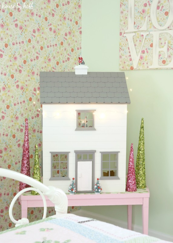 A white dollhouse with a gray room on a pink table in the bedroom.
