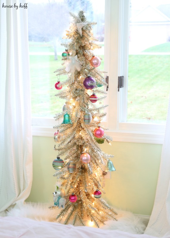 A champagne vintage Christmas tree in front of a window in bedroom.