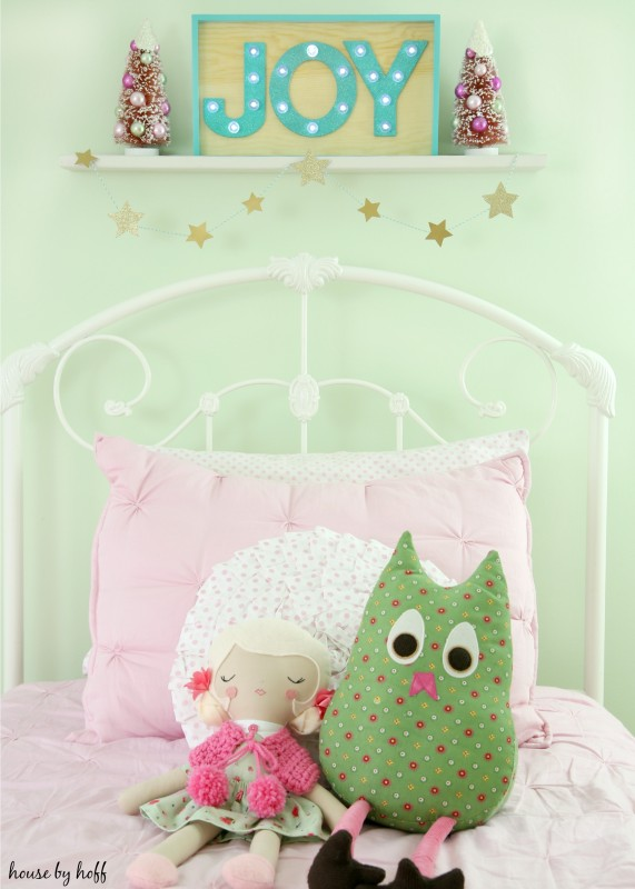 A white bed frame with pink blankets and Joy in a wooden picture frame above the bed.
