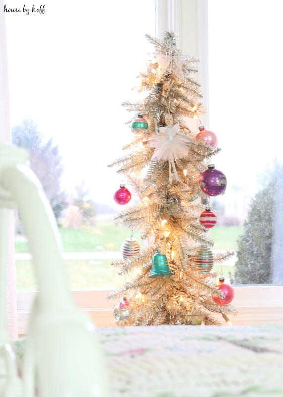 A decorated Christmas tree beside the bed in the little girl's room.