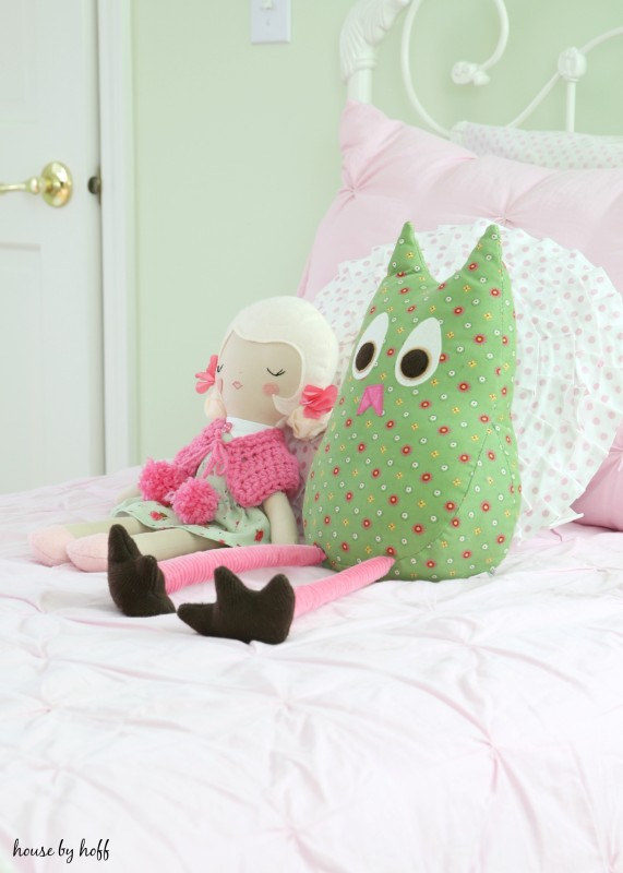 A doll and stuffed animal on the pink bed.
