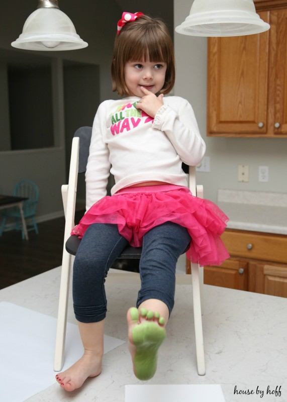 A little girl sitting on a chair with a green foot painted about to put it on the paper.