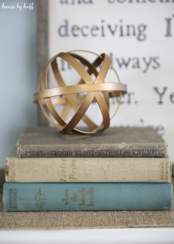 Gold geometric ball on top of vintage books.