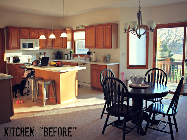 An older kitchen with wooden cabinets and dark brown table and chairs.