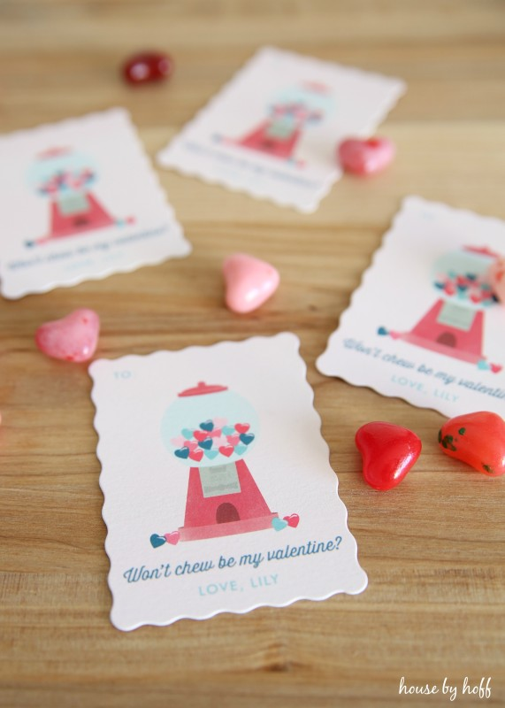 Valentines Day cards on the table with little heart candies beside them.
