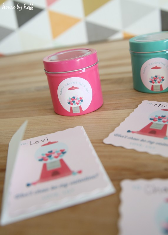 Personalized Valentines Day cards on the wooden table beside the tins.