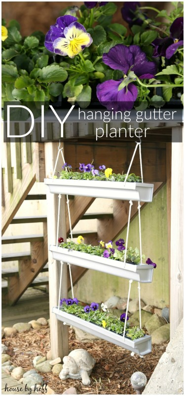A hanging gutter planter with purple flowers in it.