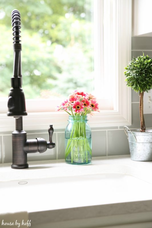 Pink flowers in glass jar beside faucet.