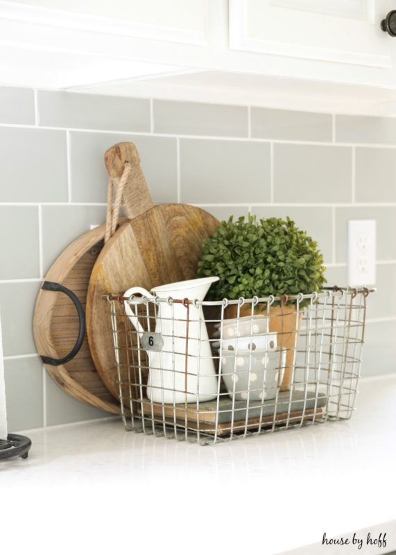 Cutting boards behind wire basket on counter.