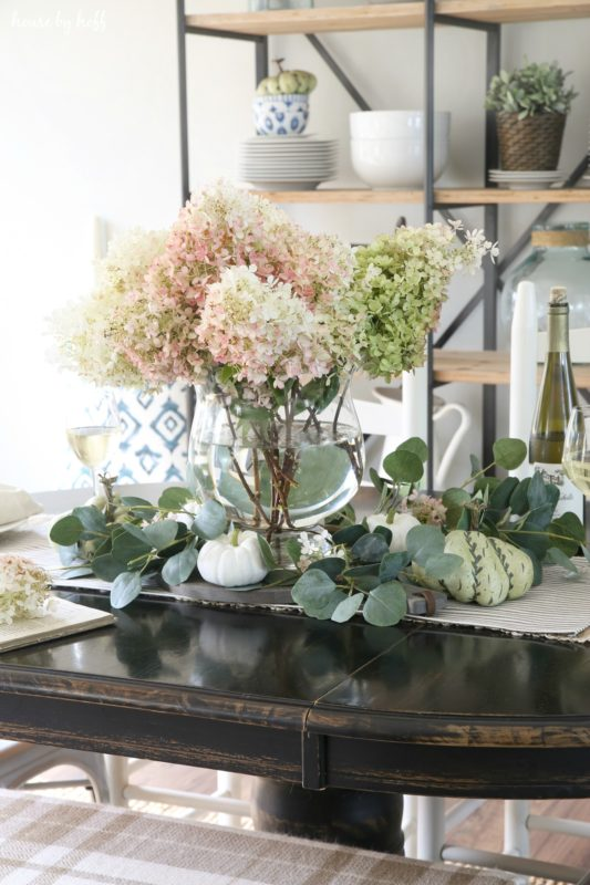 White and pink hydrangeas on table in glass vase.