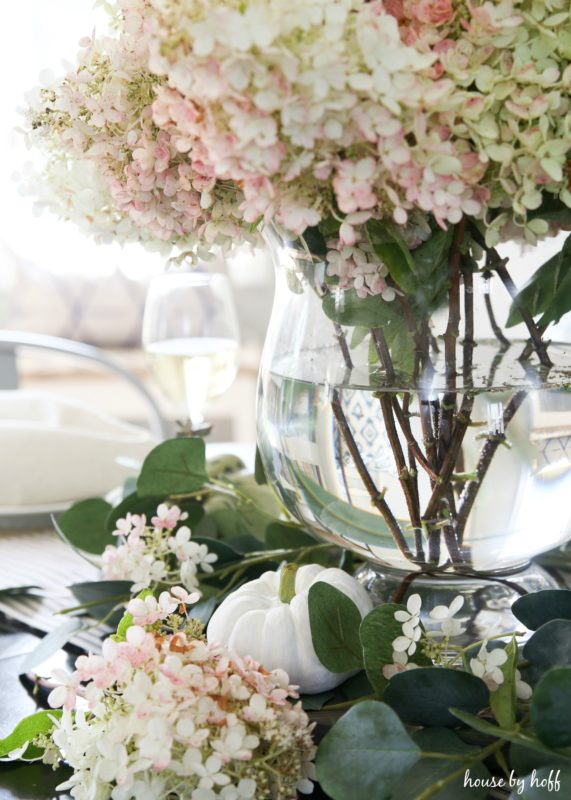 White and pink hydrangeas in vase on fall table setting.