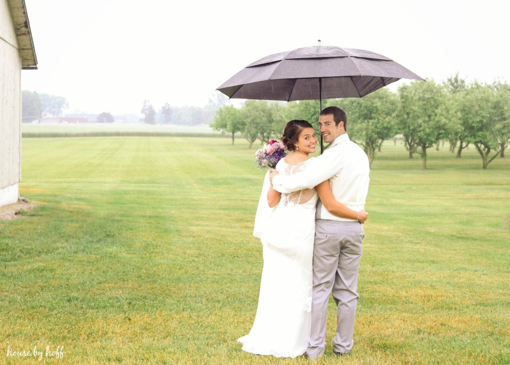 Bride and groom in a field with rain and an umbrella.