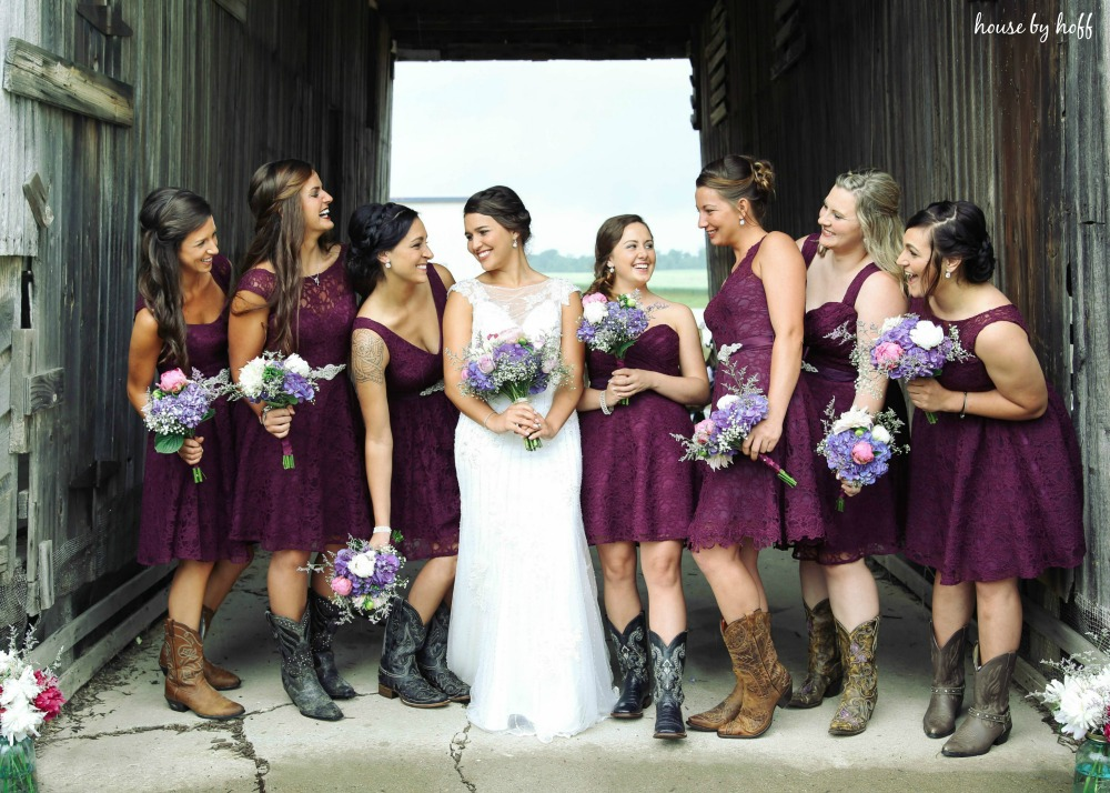 All the bridesmaids in plum dresses beside the bride.