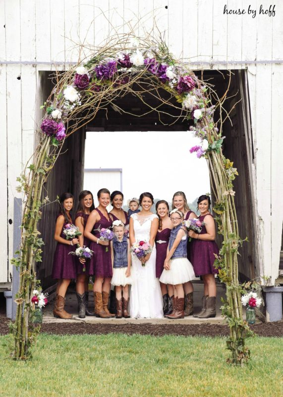 Twig and flower arch with bride and bridesmaids under it.