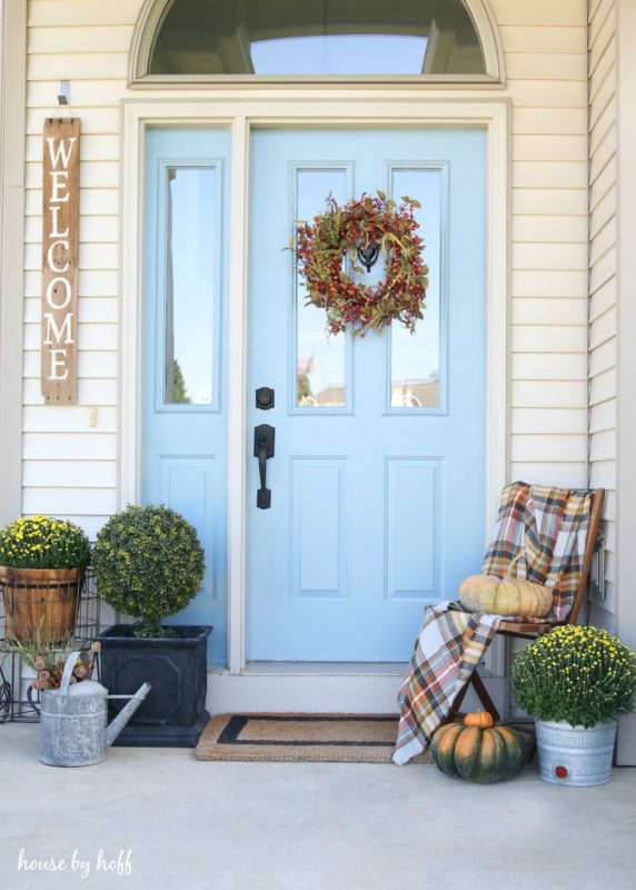 Front porch of house with a light blue door, chair, pumpkins and flowers.