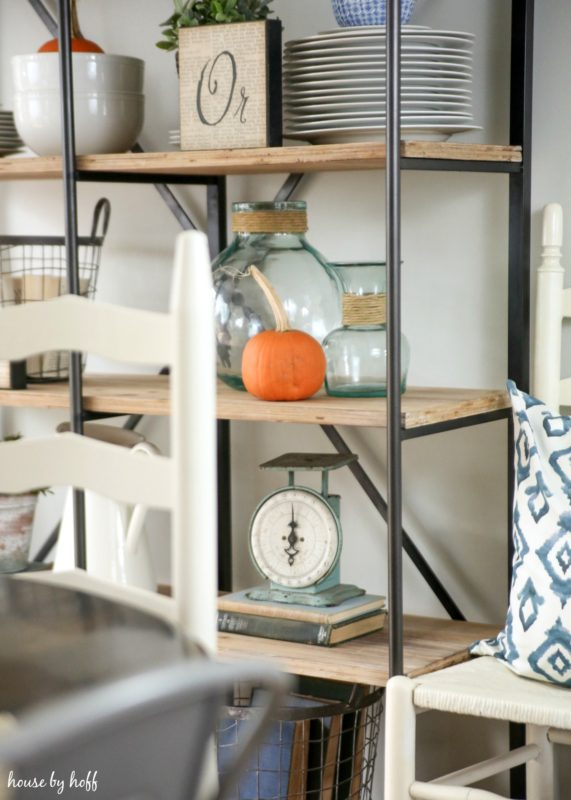 Glass jars, a scale and plates on shelving unit in dining room.