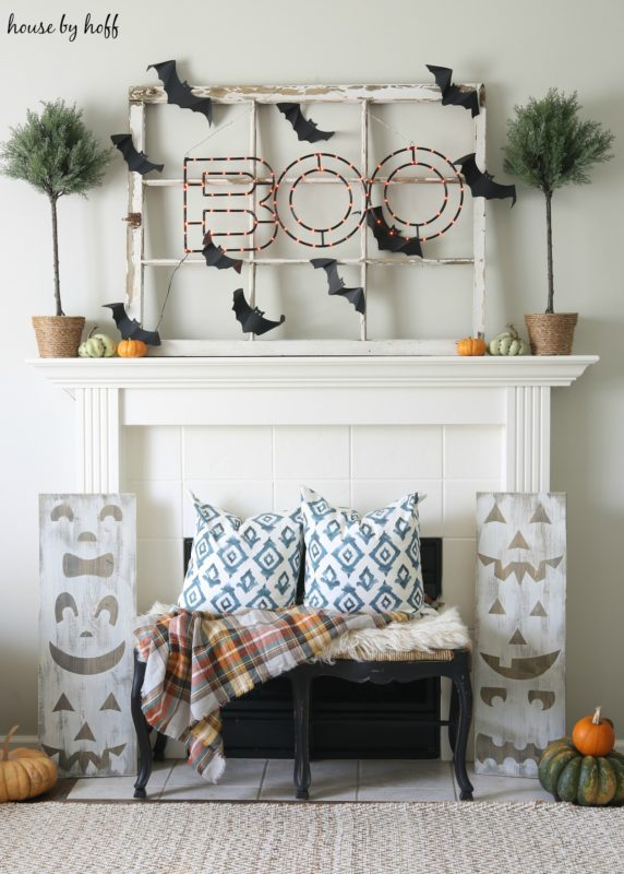 Halloween Mantel with wooden bench in front of it and blue and white pillows on it.
