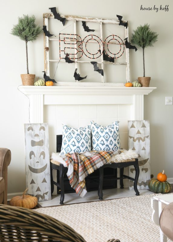 Pumpkin wooden jack'o'lantern signs in front of fireplace.