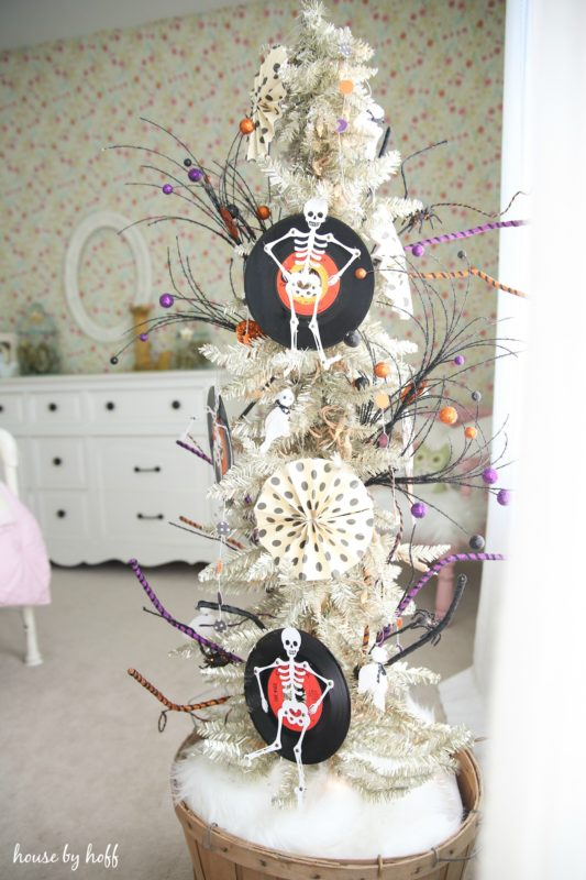 White artificial tree with skeletons and feather.