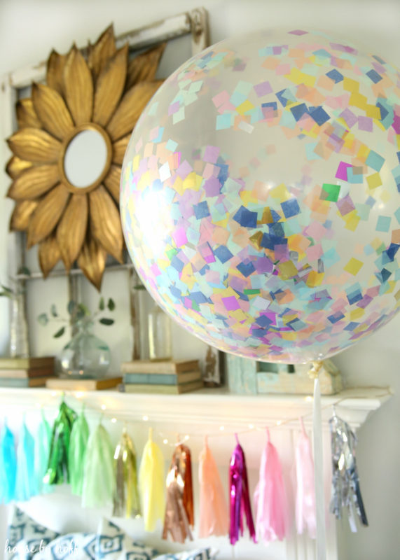Clear balloon with multi coloured bits of paper inside it hanging by the mantel.