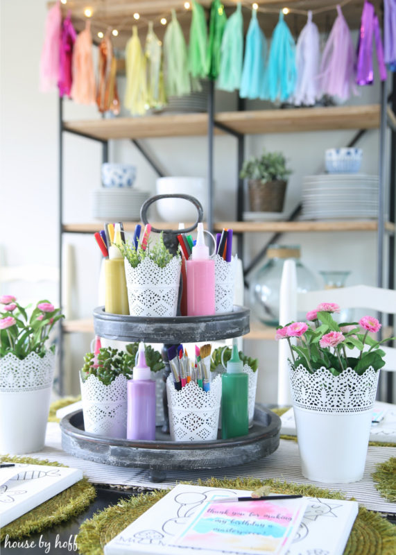 Open shelving behind table, with colourful garland.