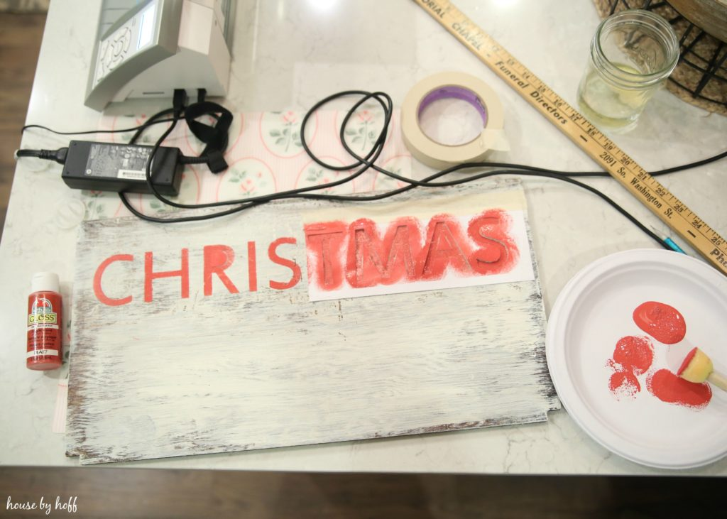 Using a stencil to make the word Christmas on the wooden board.