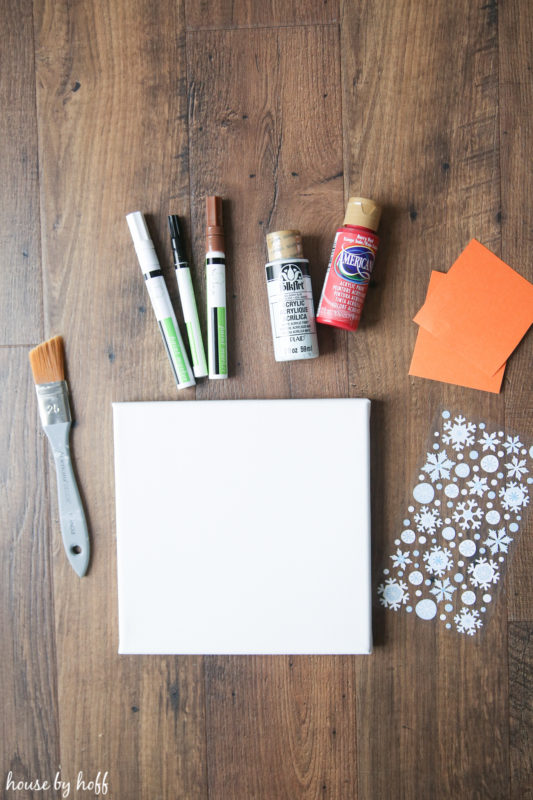 Paint, a brush, a canvas, and snowflake stickers.