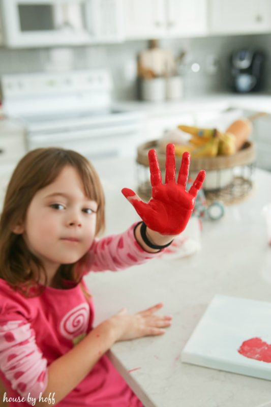 Little girl with a painted red hand.