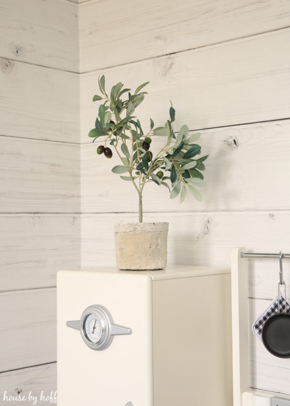 Little white play fridge with plant on top of it.