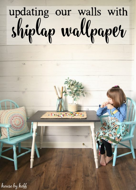 Table and chairs and little girl sitting at table in front of shiplap wall.