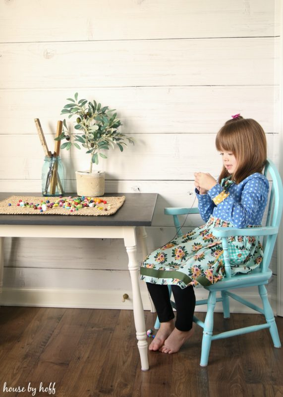A little girl sitting in her playroom stringing beads.