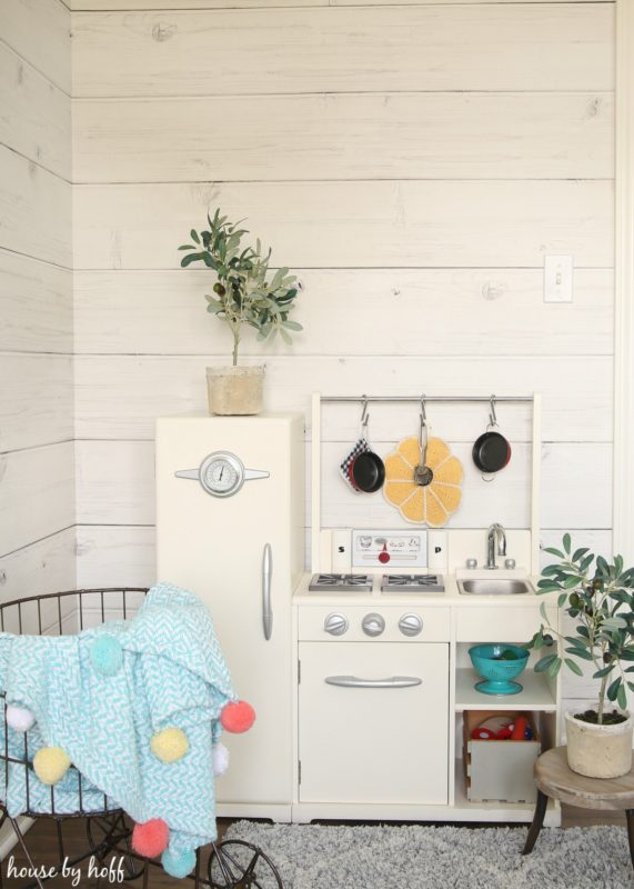 Little play kitchen for a child in front of shiplap wall.