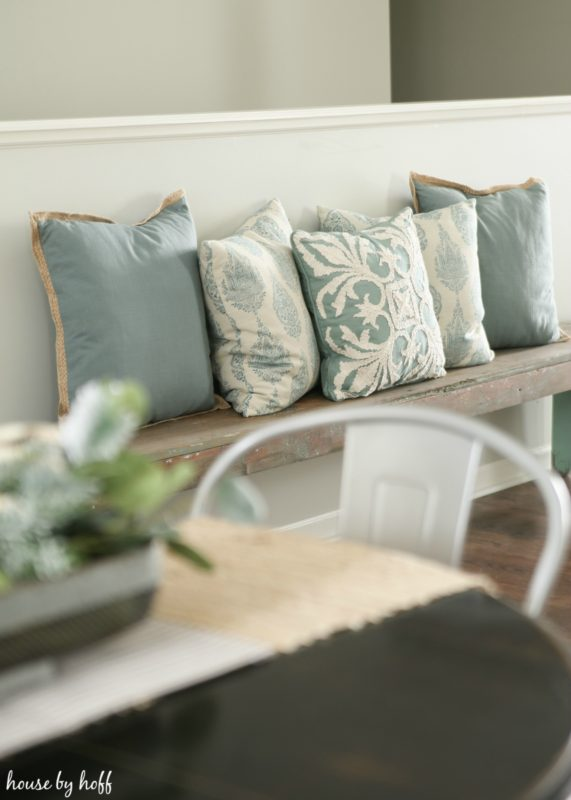 Blue and white throw pillows on wooden bench.