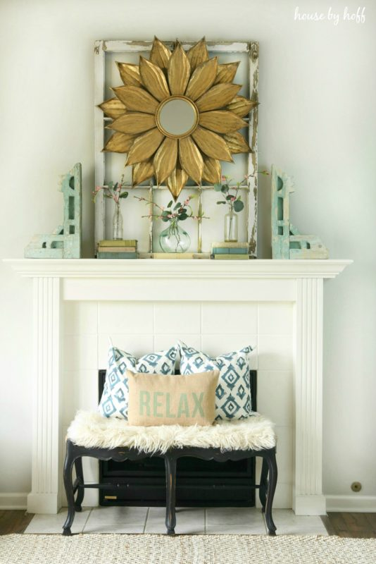 A starburst mirror on the fireplace mantel with a small bench in front of the fireplace and pillows on the bench.
