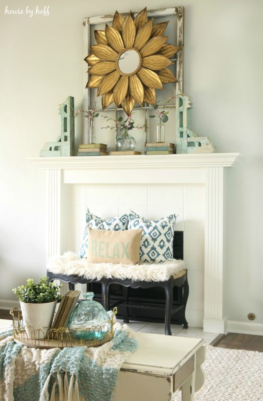 A white fireplace with a rug in front of it.