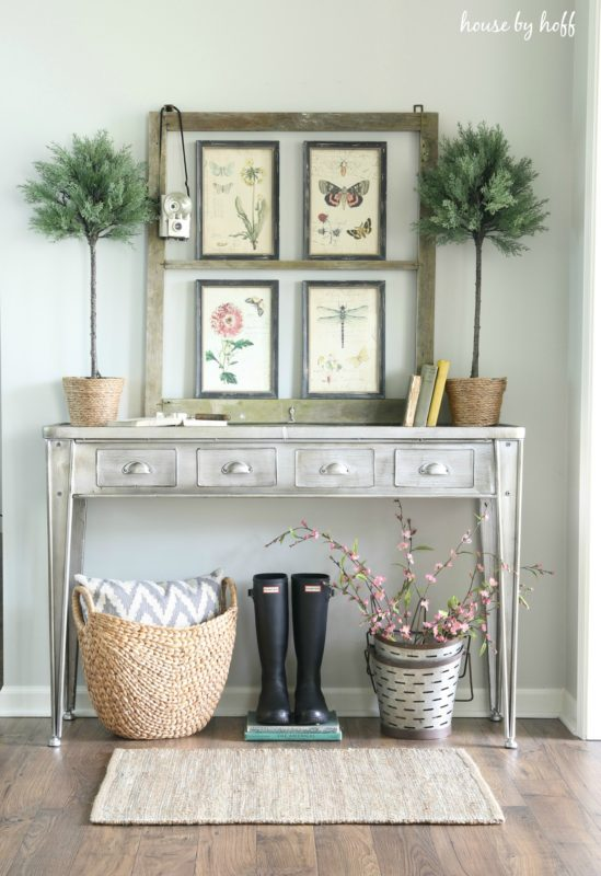Side hallway table with rubber boots underneath it and a picture frame with art in it on the table.