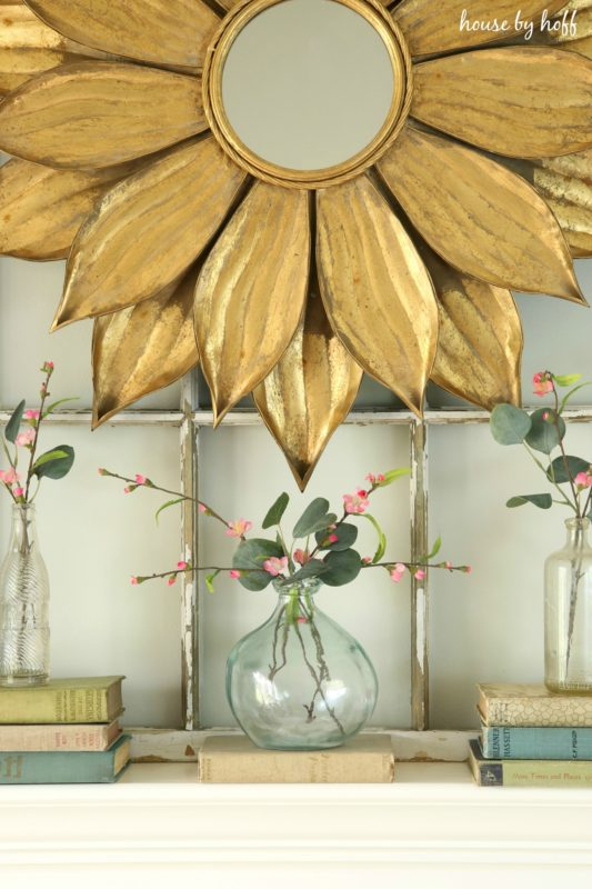Up close picture of the gold starburst mirror and clear vases filled with sprigs of pink flowers.