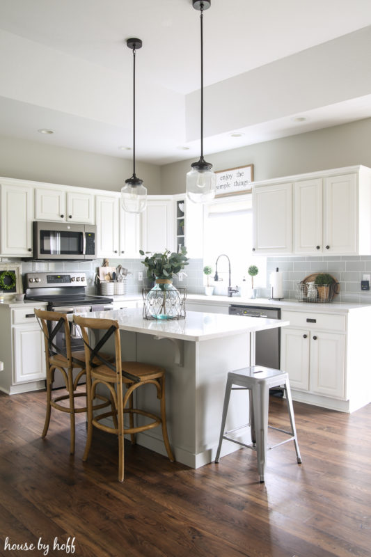 A white kitchen with white cabinets and island and a dark wood laminate floor.
