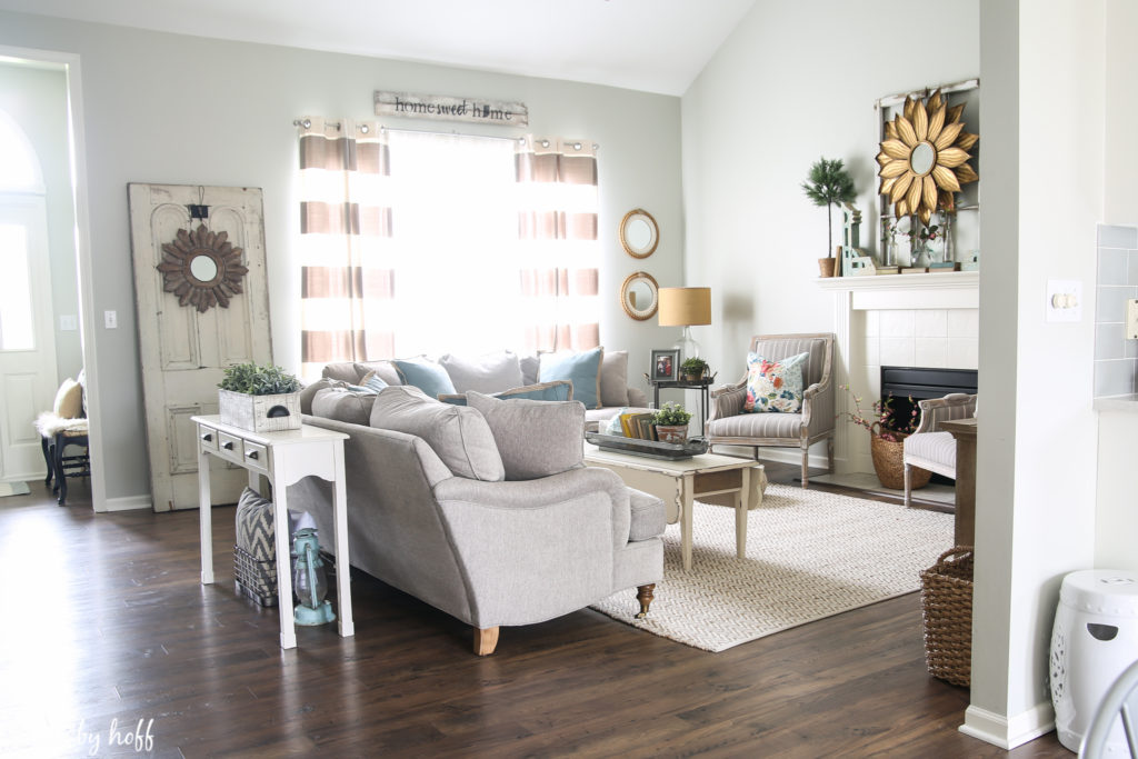 A view of the living room with laminate flooring, neutral couches and area rug.